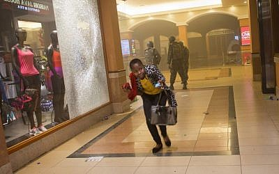 A woman runs for cover during the siege of the Westgate mall in Nairobi, Kenya, last month. (photo credit: AP/Jonathan Kalan/File)