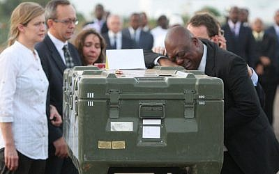 Serge Daniel, right, Mali correspondent for Radio France Internationale weeps as he pays his last respects at the coffin of one of the two French journalists kidnapped and killed Saturday in northern Mali, at a ceremony at the military airport in Bamako, Mali, on Monday (photo credit: AP/Harouna Traore)