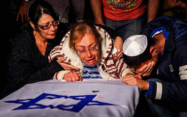 The family of Israeli soldier Eden Atias mourns over his coffin during a funeral in Nazareth-Illit , northern Israel, on Wednesday (photo credit: Avishag Shaar Yashuv/Flash90)