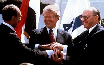 Egyptian President Anwar Sadat, left, US President Jimmy Carter, center, and Prime Minister Menachem Begin clasp hands on the North Lawn of the White House after signing the peace treaty between Egypt and Israel, March 26, 1979 (photo credit: AP/Bob Daugherty/File)