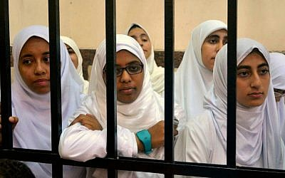 Young female supporters of ousted Egyptian president Mohammed Morsi stand inside the defendants' cage in a courtroom in Alexandria, Egypt, on Wednesday (photo credit: AP/Amira Mortada/El Shorouk Newspaper)