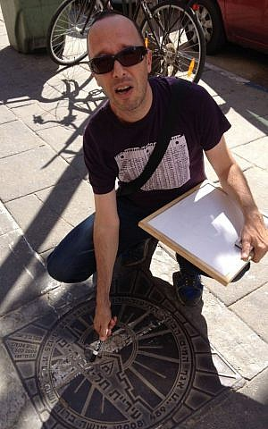 Guy Sharett finds a Hebrew lesson wherever he goes, even on manholes (photo credit: Jessica Steinberg/Times of Israel)