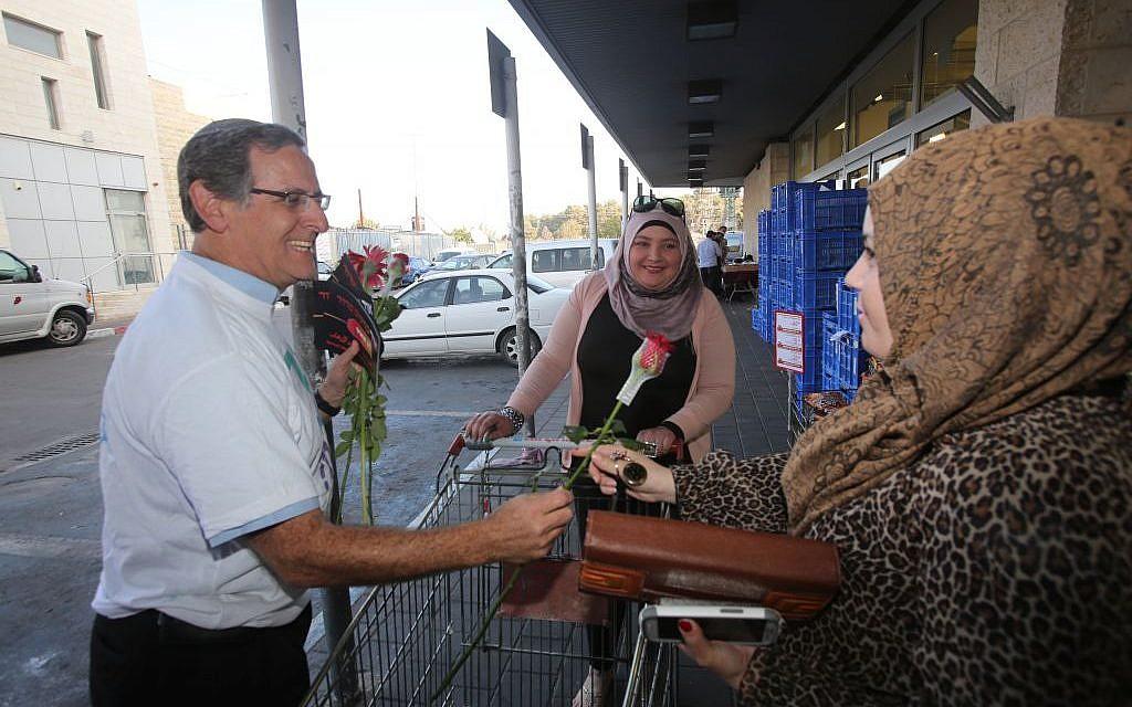 Yitzchak Glick offers a flower to a Palestinian shopper at the Rami Levi supermarket outside Alon Shvut, November 14, 2013 (photo credit: Yossi Zamir)