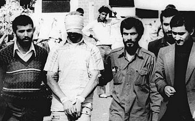 One of the hostages being held at the US Embassy in Tehran is displayed to the crowd, blindfolded and with his hands bound, outside the embassy in 1979 (AP Photo/File)