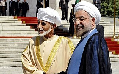 Iranian President Hasan Rouhani, right, shakes hands with Omani Sultan Qaboos during an official arrival ceremony, in Tehran, Iran, Aug. 25, 2013. (photo credit: AP/Iranian Presidency Office, Hojjat Sepahvand)