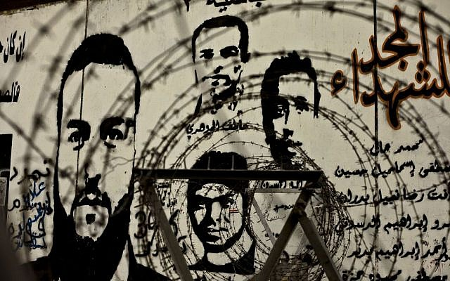 In this file photo taken Sunday, November 17, 2013, murals depicting Egyptian activists who died in anti-government protests look through barbed wire on a wall at Tahrir Square in Cairo, Egypt. Partial translation of the Arabic reads, 'Glory to the martyrs, Abassiya, Tamarod.' (photo credit: AP/Nariman el-Mofty, File)