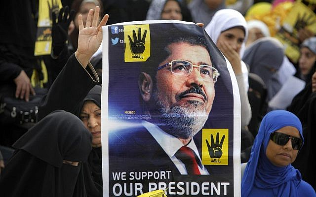 Supporters of Egypt's ousted president Mohammed Morsi raise his poster during a rally in Cairo, Egypt, on Nov. 8, 2013. The poster also shows four raised fingers, which has become a symbol of the Rabaah al-Adawiya mosque, where Morsi supporters had held a sit-in for weeks that was violently dispersed in August. (photo credit: AP/Amr Nabil)