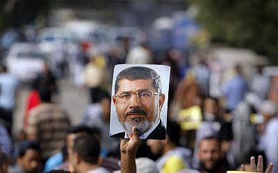 Supporters of Egypt's ousted President Mohammed Morsi raise his poster and their hands with four raised fingers, which has become a symbol of the Rabaah al-Adawiya mosque, where Morsi supporters had held a sit-in for weeks that was violently dispersed in August, during a protest in Cairo, Egypt, Friday, Nov. 8, 2013 (photo credit: AP/Amr Nabil)