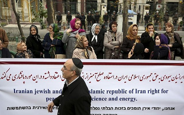An Iranian Jewish man walks past a banner during a gathering of Iran's Jewish community outside a UN office in Tehran supporting their country's nuclear program, Tuesday, November 19, 2013 (photo credit: AP/Ebrahim Noroozi)