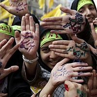 Iranian school girls raise their palms with Persian that reads 'Death to America,' during an anti-American rally in Tehran, Iran, Monday, Nov. 4, 2013 (photo credit: AP/Ebrahim Noroozi)