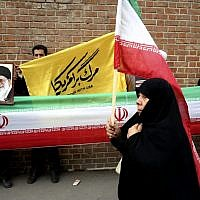 An Iranian woman walks past protesters holding an Iranian flag and photos of supreme leader Ayatollah Ali Khamenei during an annual anti-American demonstration in Tehran, Iran, Monday, Nov. 4, 2013 (photo credit: AP/Ebrahim Noroozi)