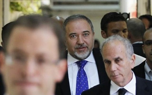 Former foreign minister Avigdor Liberman, center, walks toward a courtroom at the Magistrate's Court in Jerusalem, Wednesday, November 6, 2013 (photo credit: AP/Ronen Zvulun, Pool)