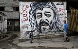 Palestinians walk past a mural depicting late Palestinian leader Yasser Arafat at the Shati Refugee Camp, in Gaza City, on November 7, 2013 (AP/Adel Hana)