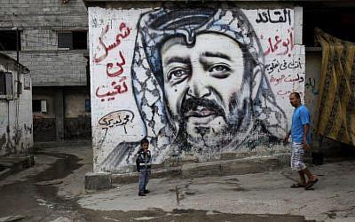 Palestinians walk past a mural depicting late Palestinian leader Yasser Arafat at the Shati Refugee Camp, in Gaza City, on November 7, 2013 (AP/Adel Hana)