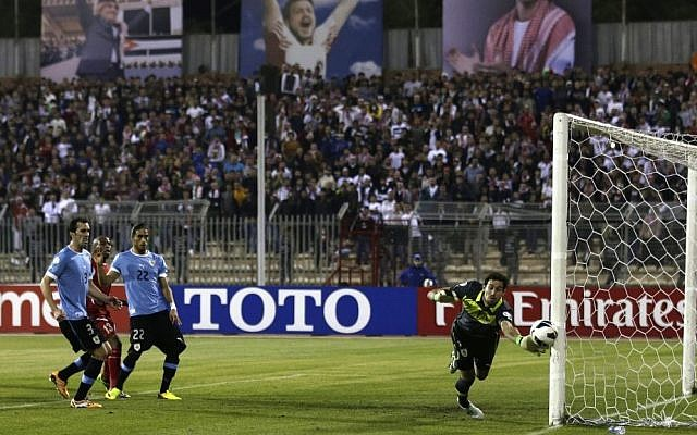 Uruguay's goalkeeper Martin Silva, right, saves a goal against Jordan during the World Cup play off first leg soccer match between Jordan and Uruguay at Amman International stadium in Amman, Jordan, on Wednesday, November 13, 2013. (photo credit: AP Photo/Hassan Ammar)