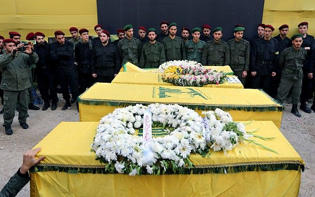 Hezbollah members stand near the coffins of four people, who were killed a day after two suicide bombings struck the Iranian Embassy in Beirut, during their funeral procession, in the southern suburb of Beirut, Lebanon, Wednesday, Nov. 20, 2013. (photo credit: AP/Bilal Hussein)