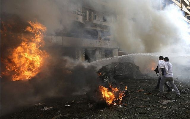 Two Lebanese men react in front of burned cars, at the scene where two explosions have struck near the Iranian Embassy killing many, in Beirut, Lebanon, Tuesday Nov. 19, 2013. (AP Photo/Hussein Malla)
