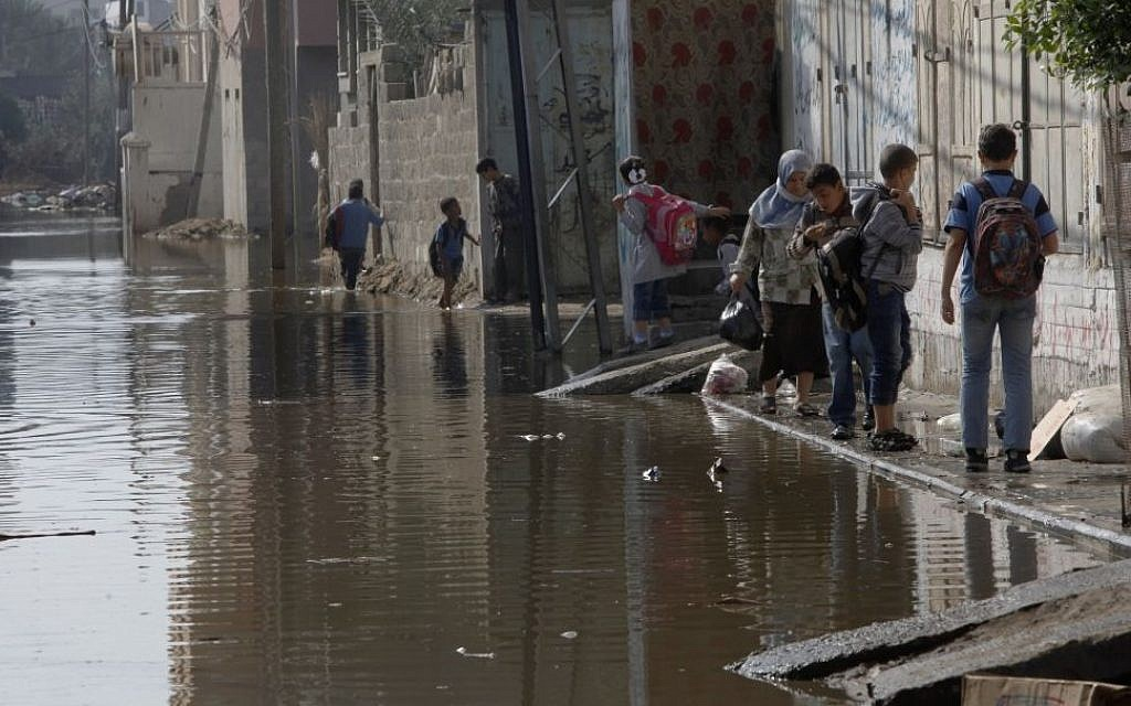 Palestinians walk on the side of a street flooded with waste water in Gaza City, Thursday, Nov. 14, 2013. A Palestinian official said sewage from a treatment plant overflowed onto streets in the Gaza Strip because of a shortage of electricity needed to process the waste. (Photo credit: AP /Adel Hana)