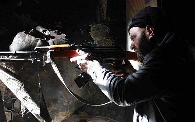A Free Syrian Army fighter aims his AK-47 as he takes his battle position in Aleppo, Syria. (Photo credit: AP/Aleppo Media Center AMC, File)