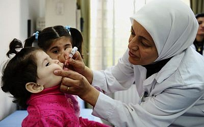 A health worker administers polio vaccine to a child as part of a UNICEF-supported vaccination campaign at the Abou Dhar Al Ghifari Primary Health Care Center in Damascus, Syria. (photo credit: AP/UNICEF, Omar Sanadiki)