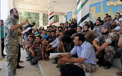 Abdul-Qadir Saleh, left, the chief commander of the Tawhid Brigade, the main rebel outfit in Aleppo province, speaks to his fighters ahead of an attack on government troops, in Aleppo, Syria, Aug. 13, 2013. (photo credit: AP/Tawhid Brigade)