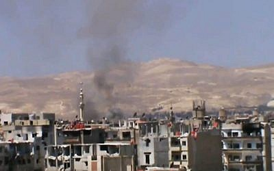 Black smoke billows in the air from heavy shelling near Damascus, Syria, on Monday, November 4, 2013 (photo credit: AP/Shaam News Network via AP video)