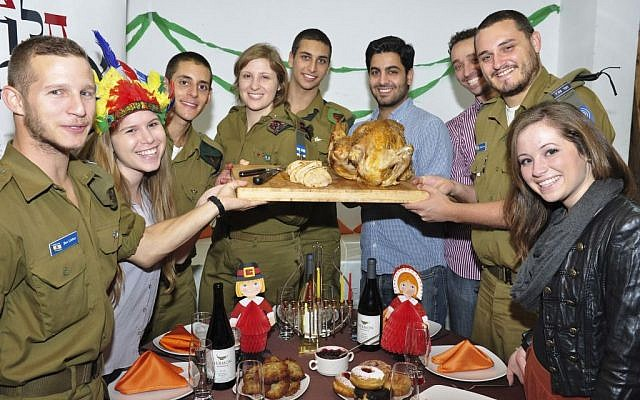Lone soldiers and young professionals gathered around a turkey at the Nefesh B'Nefesh/White City Shabbat meal in Tel Aviv Thursday. (photo Credit: Studio Tel/Courtesy of Nefesh B'Nefesh)
