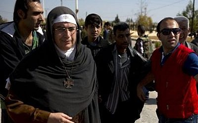 Mother Superior Agnes-Mariam Of The Cross walks with people fleeing the rebel held suburb of Moadamiyeh to the government held territory in Damascus, Syria, Oct. 29, 2013 (photo credit: AP/Dusan Vranic)