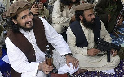 In this file photo taken Sunday, Oct. 4, 2009, Pakistani Taliban chief Hakimullah Mehsud, left, is seen with his comrade Waliur Rehman, front center, during his meeting with media in Sararogha of Pakistani tribal area of South Waziristan along the Afghanistan border. (Photo credit: AP/Ishtiaq Mehsud, File)