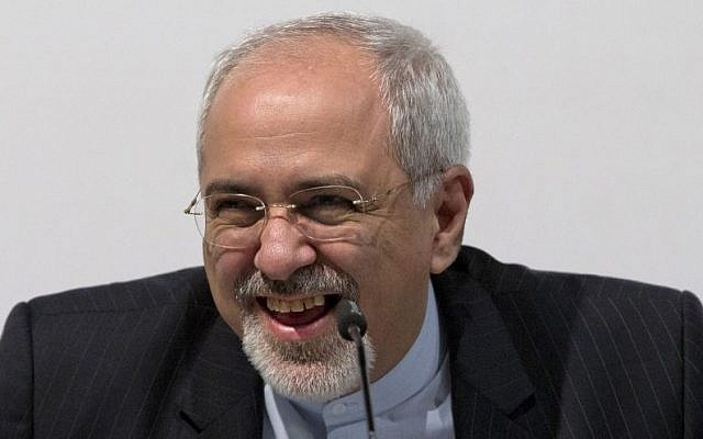 Iranian Foreign Minister Mohammad Javad Zarif smiles and laughs as he speaks to the media in Geneva, on November 24, 2013, after the interim nuclear deal was concluded (photo credit: AP/Carolyn Kaster/Pool)