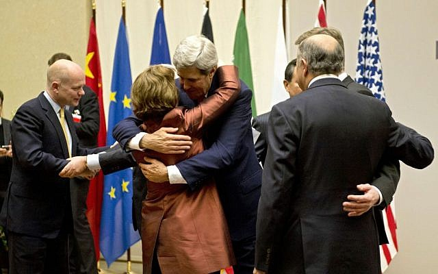US Secretary of State John Kerry, center, embraces EU foreign policy chief Catherine Ashton, during a ceremony at the United Nations after an agreement was reached on Iran's nuclear program, in Geneva, Switzerland, Sunday, Nov. 24, 2013. (Photo credit: AP Photo/Keystone, Martial Trezzini)