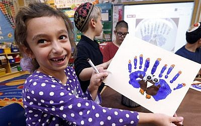 Second-grader Rozie Aronov, 7, holds up a menurkey, a paper-and-paint mashup of a menorah and turkey she created at Hillel Day School in Farmington Hills, Mich., Wednesday, Nov. 20, 2013. (photo credit: AP/Paul Sancya)