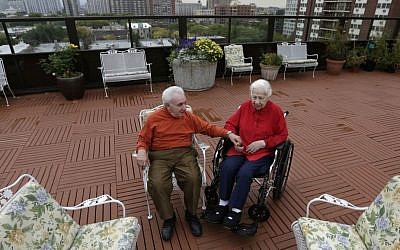 Holocaust survivors Joe Chaba, 85, and his wife, Helen, 89, sit together on the rooftop of the Selfhelp Home retirement community, in Chicago (photo credit: AP/M. Spencer Green/File)