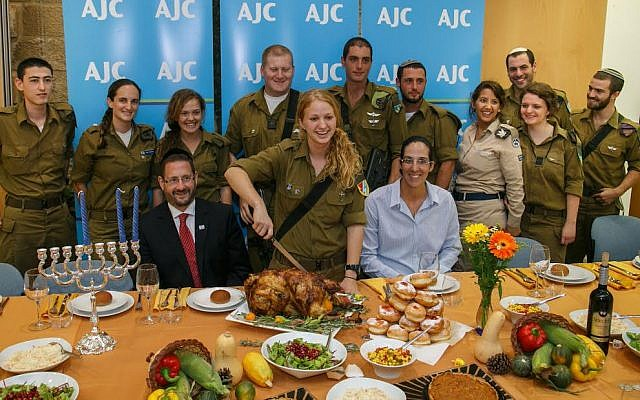 Lone soldiers including Galia Goldchain and Hannah Erdfarb with MK Dov Lipman and Paralympic athlete Moran Samuel during AJC's Thanksgiving and Hanukkah feast for lone soldiers on November 28, 2013 at the offices of AJC Jerusalem. (photo credit: Assaf Shilo/Israel Sun)