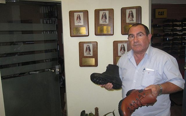 Horovitz with a Special Forces boot in his left hand and the proposed standard infantry boot in the other (Photo credit: Mitch Ginsburg/ Times of Israel)