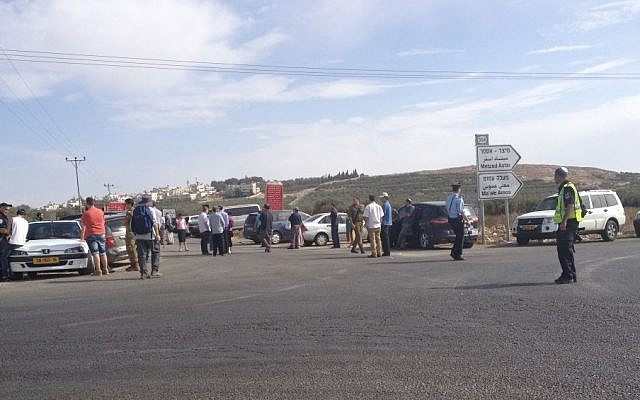 Some two dozen Gush Etzion residents held a demonstration Friday November 8, 2013 to demand better protection in the settlements. The protest came in response to a firebomb attack on a couple's car earlier in the day. The two managed to escape, sustaining light injuries. (Photo credit: Elie Leshem/Times of Israel)