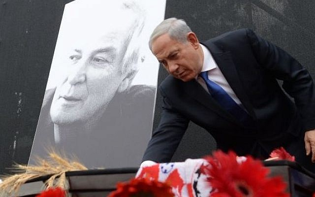 Israeli Prime Minister Benjamin Netanyahu lays a flower on the coffin of Israeli legendary singer Arik Einstein. (photo credit: Kobi Gideon/GPO/FLASH90)