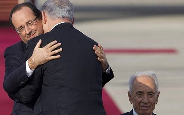 French President Francois Hollande, left, hugs Israel's Prime Minister Benjamin Netanyahu as Israel's President Shimon Peres looks on, upon Hollande's arrival in Ben Gurion airport near Tel Aviv, Sunday, November 17, 2013 (photo credit: AP/Ariel Schalit)