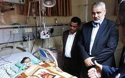 Hamas Prime Minister Ismail Haniyeh visits his granddaughter Aamal at a hospital in Gaza (photo credit: Facebook image)