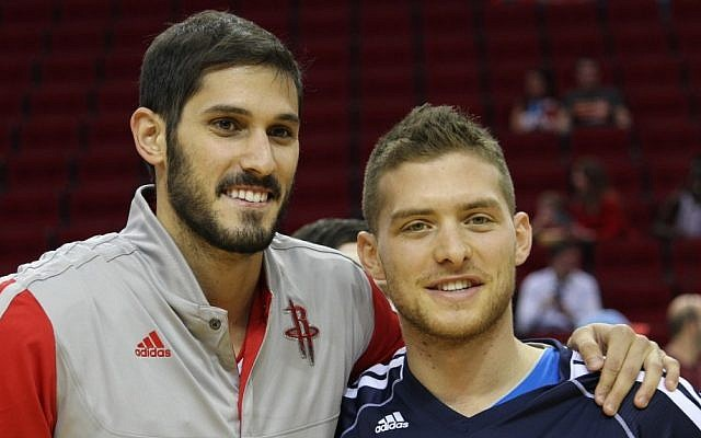 Israelis Omri Casspi, left, of the Houston Rockets and Gal Mekel of the Dallas Mavericks sharing a friendly moment at the Toyota Center in Houston before their teams squared off in a preseason game, Oct. 21, 2013. (Hillel Kuttler)