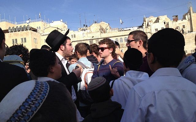 Protesters arguing with Women of the Wall supporters at the Western Wall plaza Monday. (photo credit: Debra Kamin / Times of Israel staff)