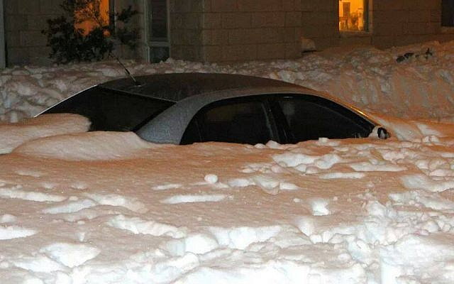 A snow-covered car in the settlement of Neve Daniel, just south of Jerusalem, Saturday night, December 14, 2013 (photo credit: Laura Ben-David)