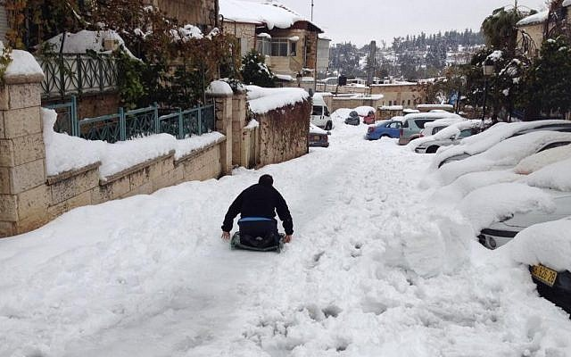 Residents of Jerusalem's Nachlaot neighborhood use a garbage bin lid as a makeshift sled to slide down a street blanketed with snow on Saturday, December 14, 2013. (photo credit: Roy Ben-Baruch/The Times of Israel)