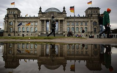 The Reichtag building, which hosts Germany's parliament Bundestag, is reflected in a puddle on a rainy autumn day in Berlin, Germany, Monday, Nov. 4, 2013. (AP Photo/Markus Schreiber)