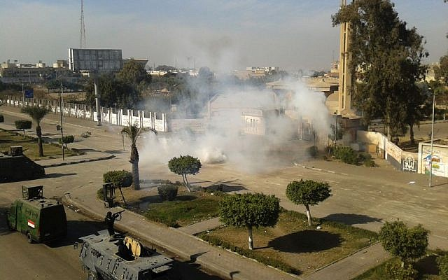 Egyptian security forces fire tear gas to disperse supporters of ousted president Mohammed Morsi as they protest at Al-Azhar University in Cairo, Egypt, Friday, Dec. 27, 2013. (Photo credit: AP/Mohamed Hassan)