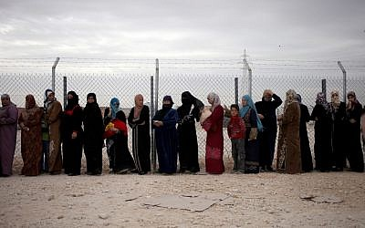 File photo: Syrian refugee women stand in line to receive their family's share of winter aid kits at the Zaatari refugee camp, near the Syrian border. (photo credit: AP/Mohammad Hannon)