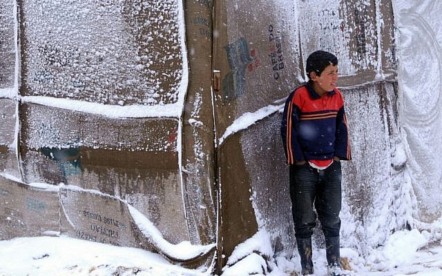 A Syrian refugee boy stands outside his tent as a heavy snowstorm batters the region, in a camp for Syrians who fled their country's civil war, in the Bekaa valley, eastern Lebanon, Wednesday, Dec. 11, 2013. (photo credit: AP)