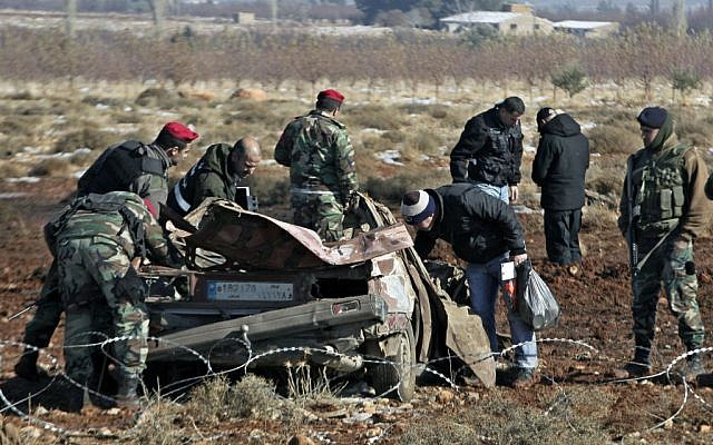 Lebanese army investigators inspect at the scene where a car bomb went off next to a Hezbollah base near the village of Sbouba in the Baalbek region pg eastern Lebanon, early Tuesday, December 17, 2013. (photo credit: AP Photo/Bilal Hussein)