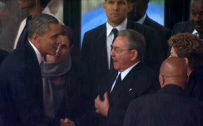 In this image from TV, U.S. President Barack Obama shakes hands with Cuban President Raul Castro at the FNB Stadium in Soweto, South Africa, in the rain for a memorial service for former South African President Nelson Mandela, Tuesday Dec. 10, 2013. (photo credit: AP Photo/SABC Pool)