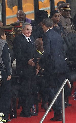 US President Barack Obama shakes hands with Cuban President Raul Castro at the FNB Stadium in Soweto, South Africa, in the rain for a memorial service for former South African President Nelson Mandela, Tuesday Dec. 10, 2013. (photo credit: AP Photo)